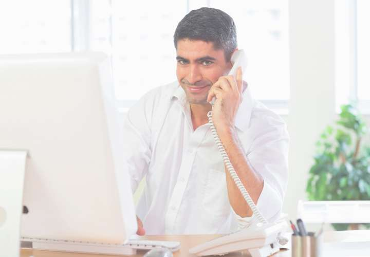 Businessman using telephone and computer